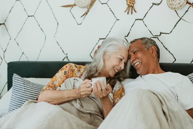 침대에서 모닝 커피를 마시는 쾌활한 노인 부부