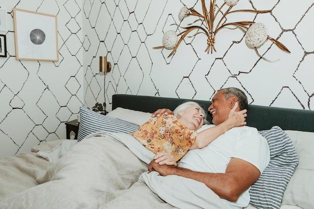 침대에서 쾌활한 노인 부부