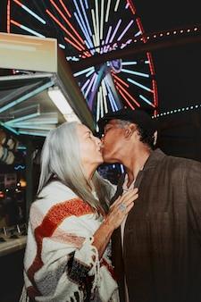 カリフォルニア州サンタモニカのパシフィック公園でキスする陽気な老夫婦