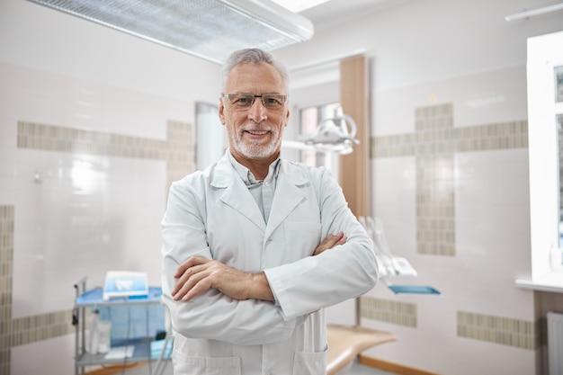 카메라를 웃고있는 동안 그의 팔이 그의 가슴에 교차하는 실험실 코트를 입고 쾌활한 노인 치과 의사