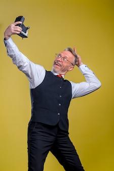 陽気な年配の白髪の口ひげのひげを生やした男。黄色の背景に分離。人々のライフスタイルの概念。上から携帯電話で自分撮りをする