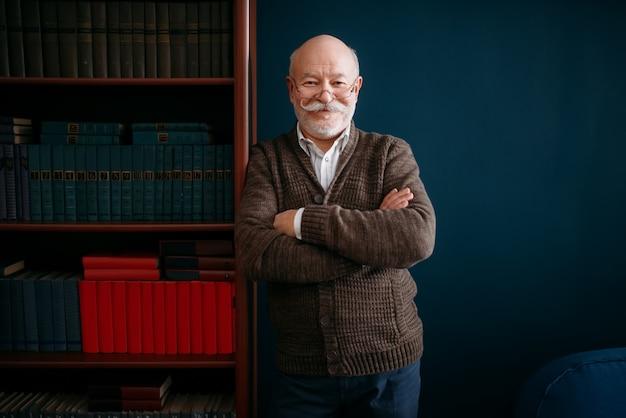メガネで陽気な老人は、ホームオフィスの本棚でポーズします。ひげを生やした成熟したシニアポーズリビングルーム、老年実業家