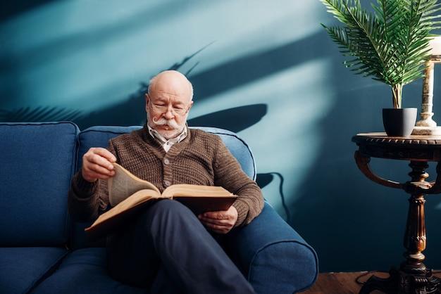 Веселый пожилой мужчина в очках читает книгу на диване в домашнем офисе