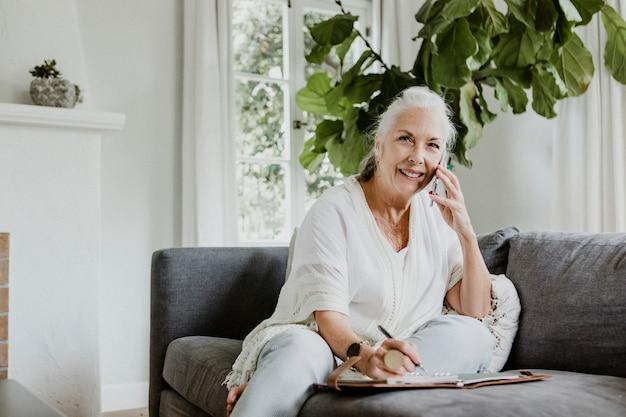 Веселая пожилая женщина разговаривает по телефону на диване