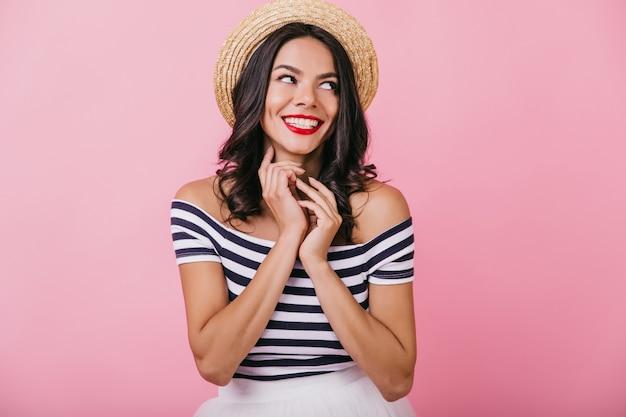 笑っているレトロな帽子の陽気なエレガントな女の子。夏服を着た肌寒い日焼けした女性の肖像画。