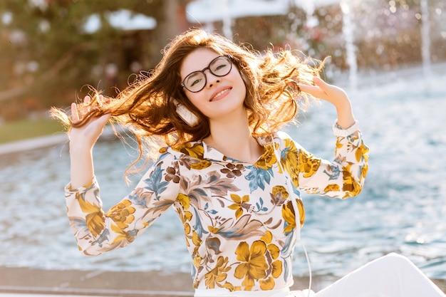 Веселая элегантная дама играет со своими вьющимися волосами и наслаждается жизнью в солнечный день