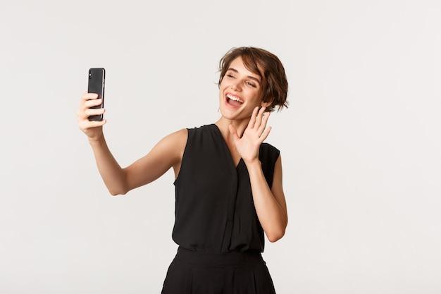 Веселая элегантная женщина здоровается во время видеозвонка, машет на камеру смартфона и улыбается, стоя белым.