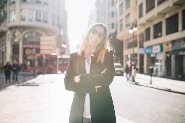 Cheerful elegant young woman with sunglasses on street in sunny day