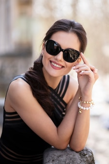Cheerful elegantly beautiful brunette young woman, in elegant black dress and sunglasses, posing outside, touching her hands together on the balcony.