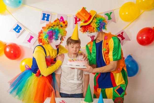 아이들과 함께 휴일에 쾌활한 감정적 인 광대가 케이크를 날려 버린다.