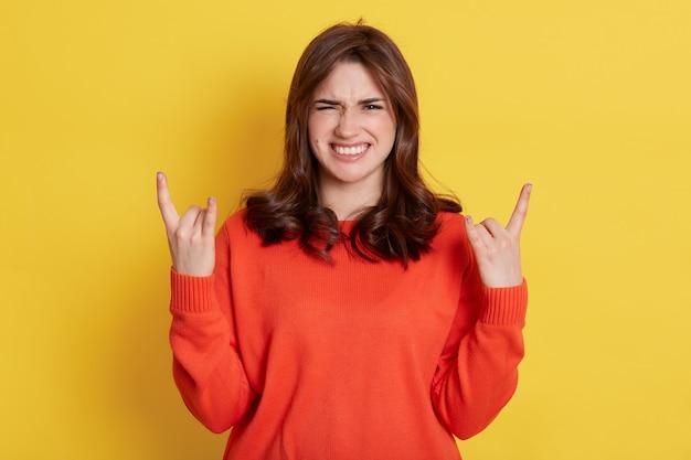Веселая эмоциональная темноволосая самка делает рок-н-ролльный жест и громко кричит, возбужденная дама со счастливым хмурым лицом позирует поверх желтого.