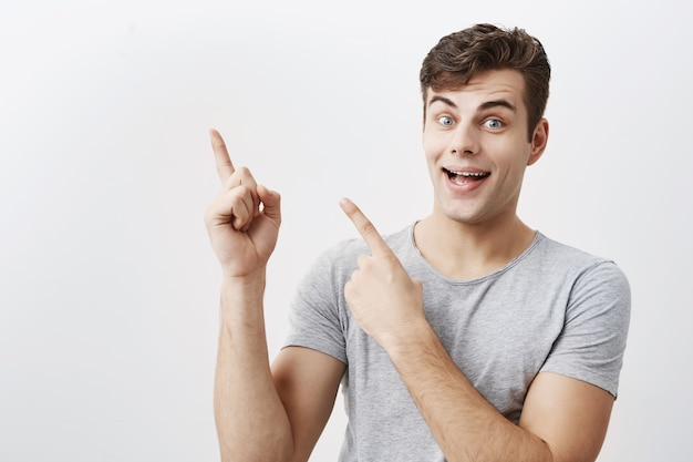 Cheerful emotional handsome man indicates happily sidewards, smiling broadly with teeth, has positive expression. good-looking male pointing at blank space for your advertisment or promotional text