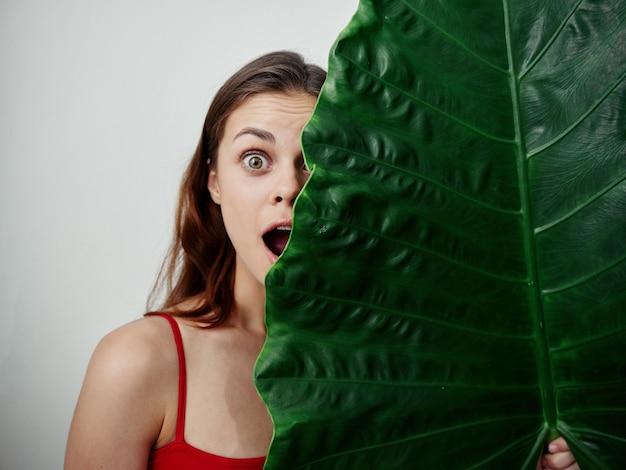 陽気な感情的な女性の大きな緑の葉が彼女の顔の赤い水着を覆っている