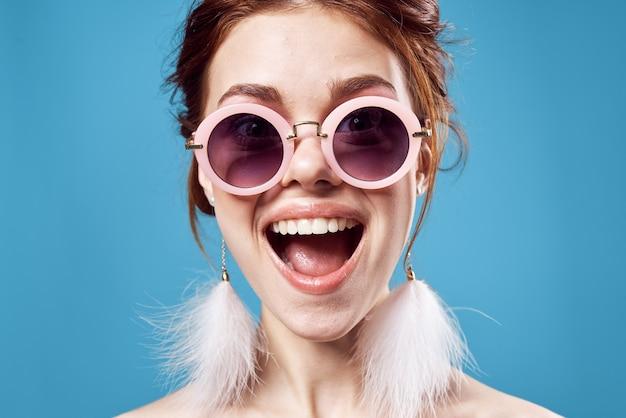 선글라스 패션 밝은 메이크업 장식 파란색 배경을 입고 쾌활한 감정적 인 여자. 고품질 사진