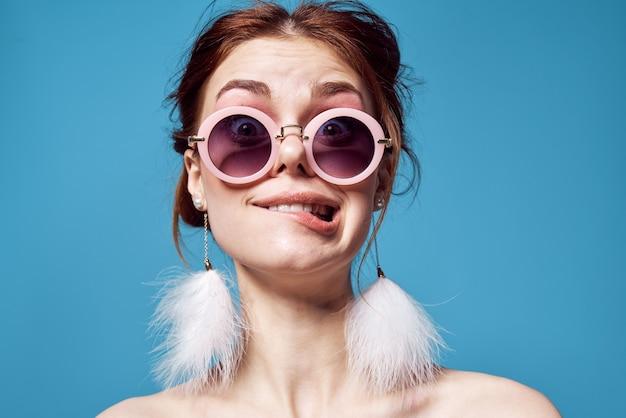 サングラスファッション明るい化粧装飾青い背景を身に着けている陽気な感情的な女性