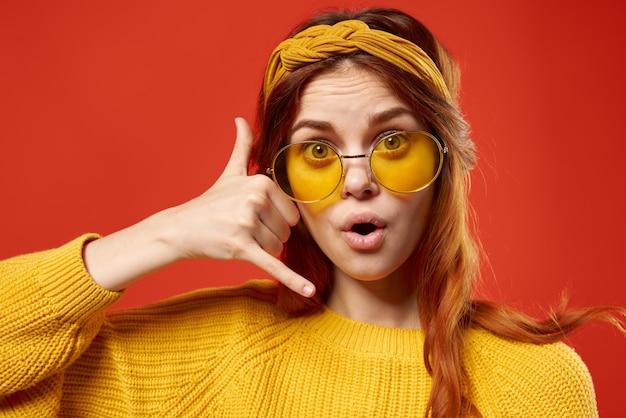 メガネの黄色いセーターのクローズアップ赤い壁を持つ陽気な感情的な女性。