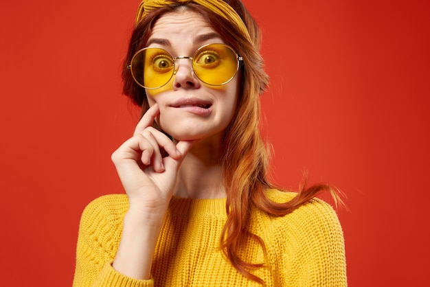 Cheerful emotional woman with glasses yellow sweater close-up red.