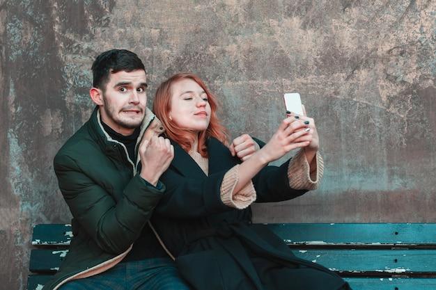 쾌활한 감정적인 젊은 부부는 벤치에 앉아 셀카를 찍는다