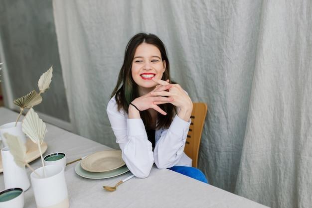 Веселая эмоциональная молодая женщина, сидящая за деревянным столом с тарелками на кухне дома