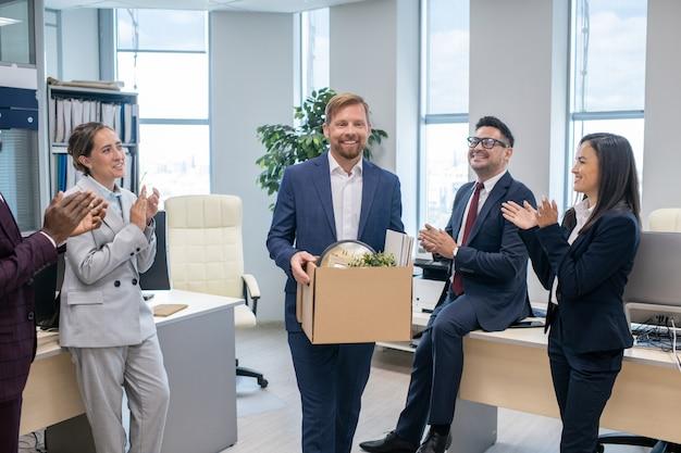 동료들 사이에서 상자를 들고 박수를 치는 쾌활한 직원