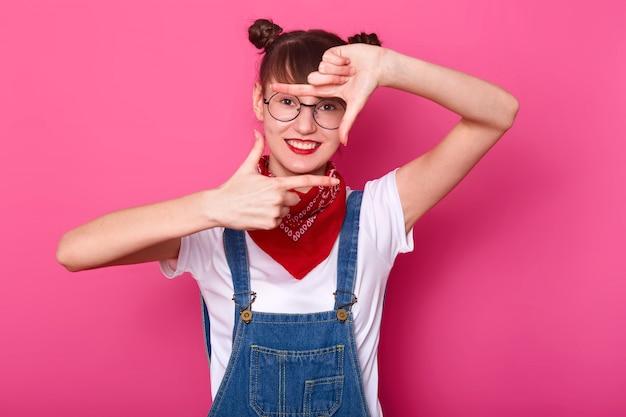 写真を作る、自分の前に手を置く陽気なエネルギッシュな女性