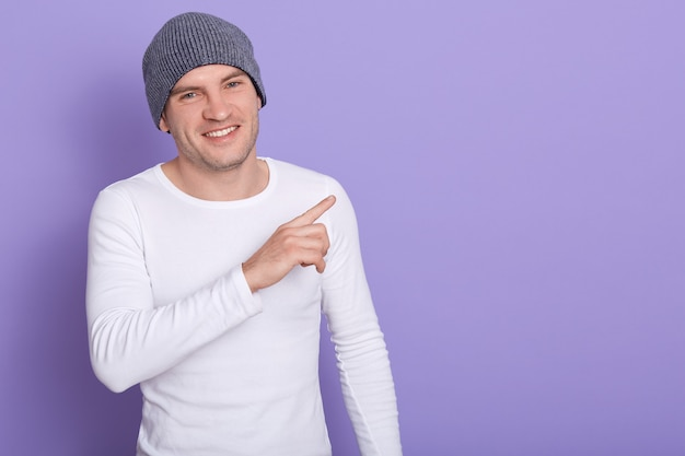 Cheerful energetic man having pleasant facial expression, making gesture with forefinger, smiling sincerely, being in high spirits. copyspace for advertisement.