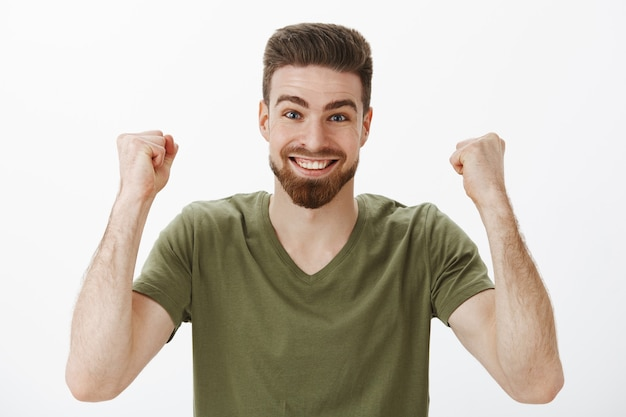 Cheerful and energized active cute male fan with beard in t-shirt raising clenched fists in victory and triumph celebrating win of first prize smiling from excitement and delighted over white wall