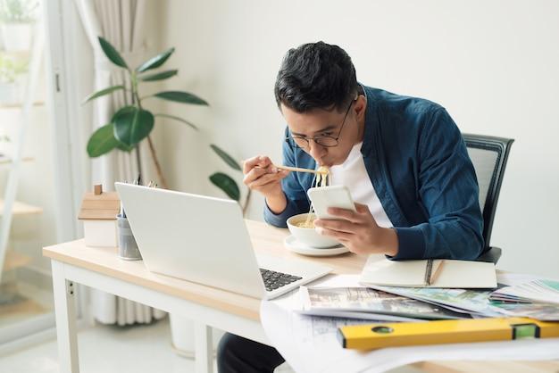 Веселый инженер с десертом сидит перед монитором компьютера и ест лапшу