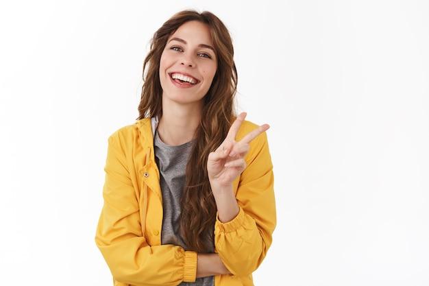 陽気な熱狂的なゴージャスな女性の巻き毛の栗の髪型は、明るい楽観的な気分で立っている白い壁を持ってのんびりと笑って笑って勝利のジェスチャーを示しています夏をお楽しみください