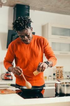 Веселый восторженный мужчина улыбается и держит деревянную ложку, добавляя специи в сковороду