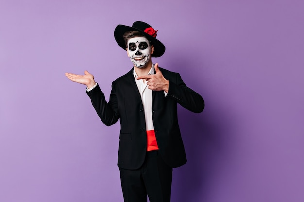 Cheerful, enthusiastic man with painted face for halloween points his finger at place for text on purple background.