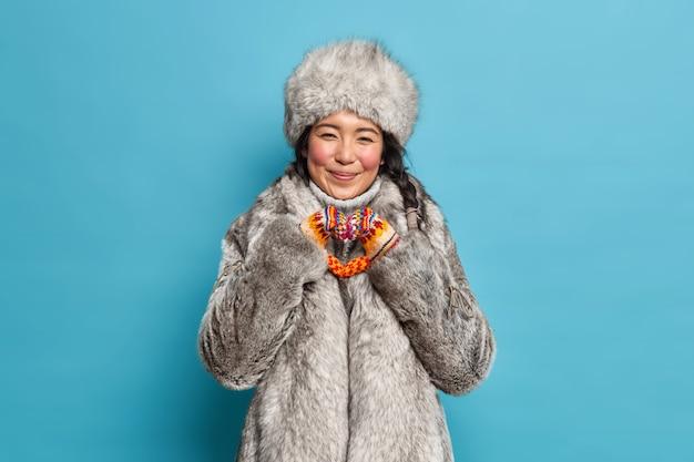 陽気なエスキモの女性の形のハートのジェスチャーは、青い壁に隔離された暖かい冬の服に身を包んだ愛を表現します
