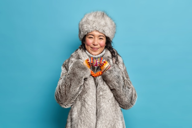 Cheerful eskimo woman shapes heart gesture expresses love dressed in warm winter clothing isolated over blue wall