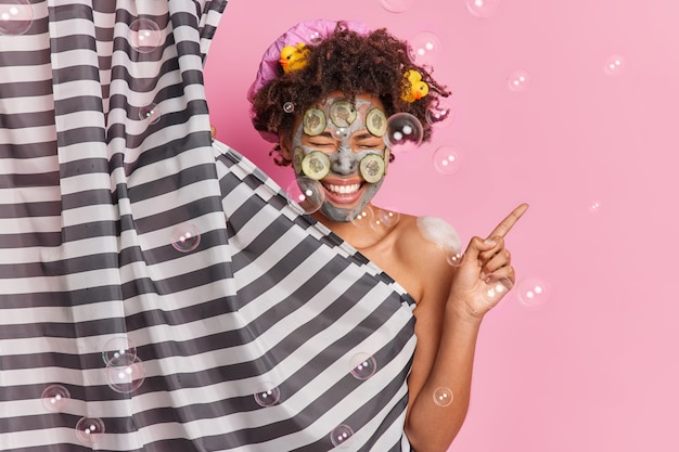 Cheerful ethnic female applies beauty mask on face indicates aside poses at bathroom going to take shower giggles positively has clean body healthy groomed skin.