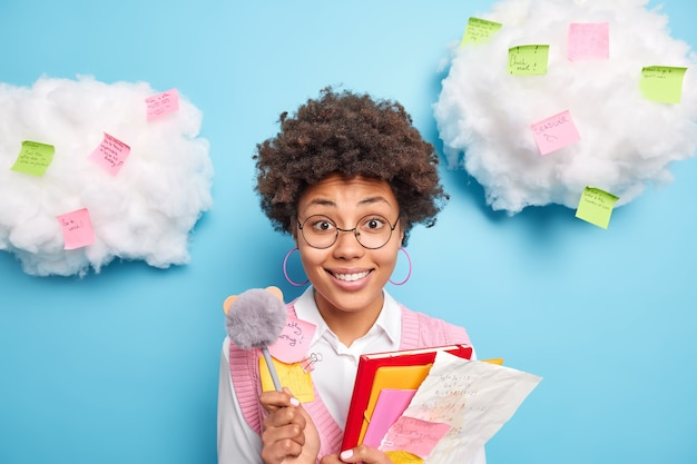 Cheerful ethnic female college student holds paper folders and pen going to unveristy on lectures wears round spectacles formal clothes surrounded by colorful stickers isolated over blue wall