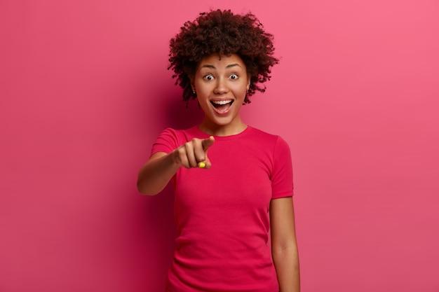 陽気な民族の女の子が人差し指であなたを指さし、誰かを選び、幸せそうに笑い、ピンクのtシャツを着て、真っ赤な壁に立って、楽しく笑います。うわー、なんてすごいことだ!