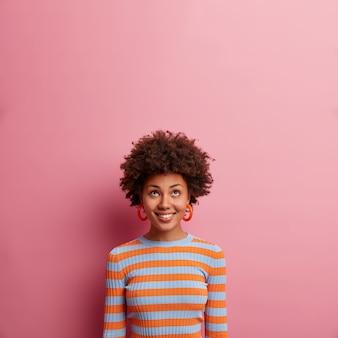 巻き毛の陽気な民族の女の子、上に集中し、気分が良く、不思議なことに上向きに見え、カジュアルなストライプのジャンパーを着て、ピンクの壁に隔離され、空きスペース