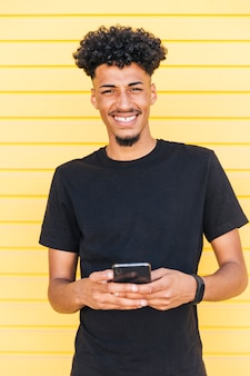 Cheerful ethnic man using phone