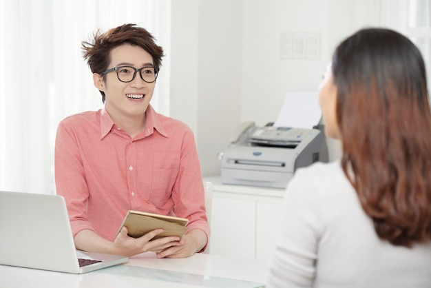 Cheerful ethnic man with coworker at table