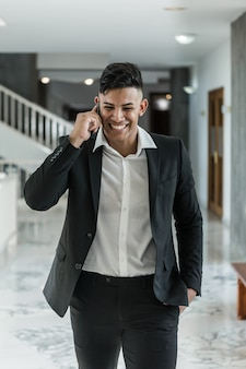 Cheerful ethnic manager speaking on phone in corridor