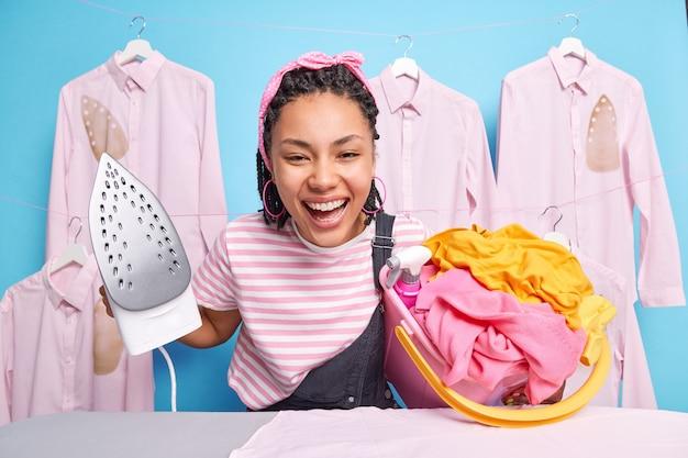 陽気なエスニックミレニアル世代の女の子は、母親が家の仕事をするのを助けます洗濯物入れバスケットises電気アイロンは青い壁に隔離された毎日の家庭のルーチンで忙しい気分です