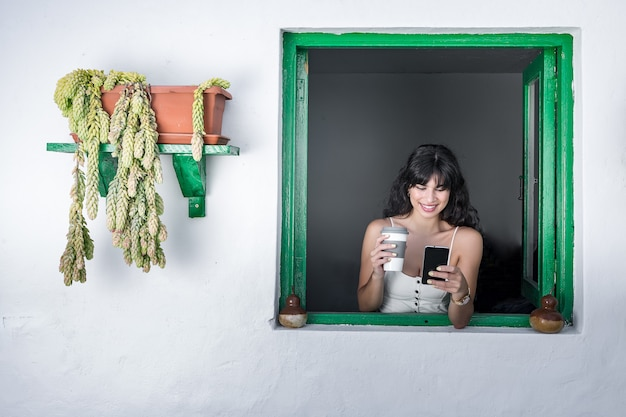 Cheerful ethnic woman with drink to go using smartphone in window