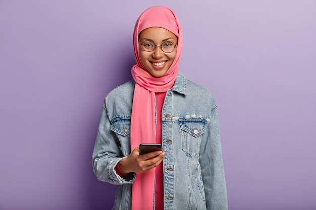 Cheerful ethnic woman with gentle smile, scrolls news feed in internet on mobile phone, reads interesting invitation message, dressed in pink hija and round spectacles, isolated over purple wall