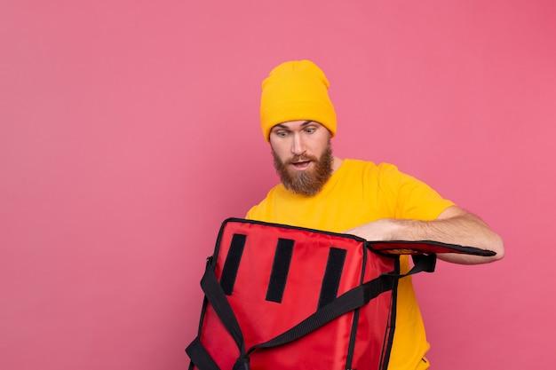 쾌활한 유럽 수염 배달 남자 놀란 감정 분홍색에 음식 상자 열기