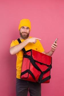 Веселый европейский доставщик с сумкой, повседневный телефон, указывая пальцем на экран на розовом