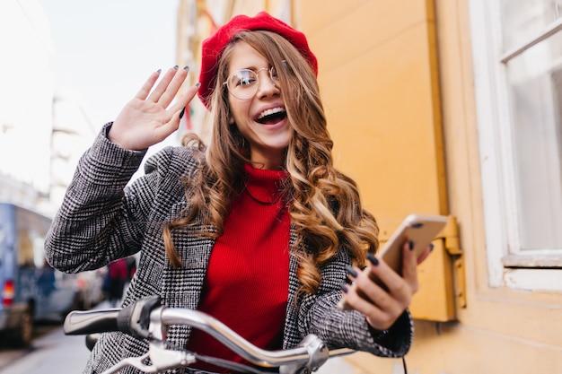 通りを走り回って、幸せな感情を表現する面白い赤いベレー帽の陽気なヨーロッパの女性モデル
