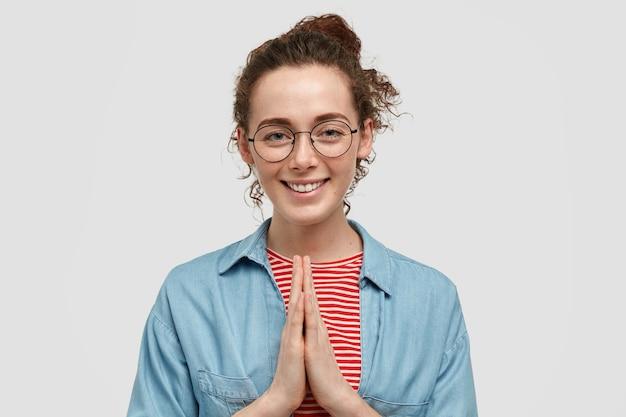 そばかすが顔に付いている陽気なヨーロッパの女性は、祈りのジェスチャーで手を保ち、何か良いものを信じて、白い壁に隔離された優しい笑顔を持っています。
