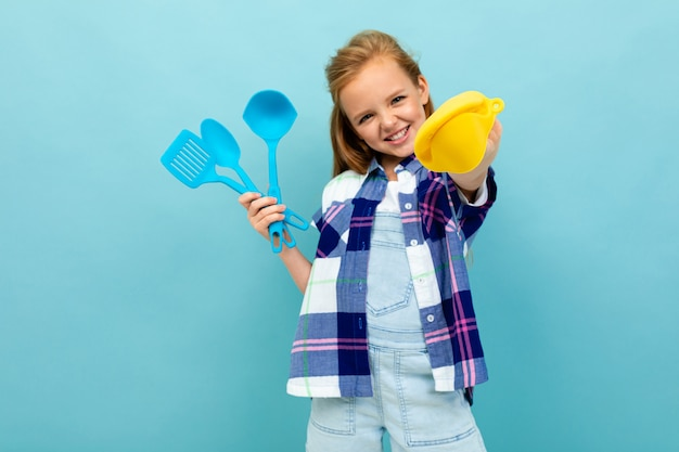 Cheerful european girl holding a oven mitts and cutlery in hands on light blue