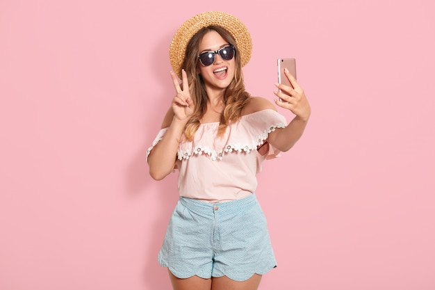 Cheerful european girl makes selfie isolated over pink studio wall, woman in shirt with bare shoulders, short, sunglasses and hat shows peace gesture in front of camera, takes picture of herself