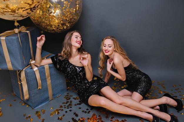 Веселая европейская девушка со светлыми волосами наслаждается вечеринкой по случаю дня рождения с друзьями. фотография в помещении утонченной женской модели с ярким макияжем, лежащей на конфетти рядом с подарками и смеющейся.